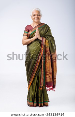 Smiling senior Indian woman holding hands in Namaste mudra - stock photo
