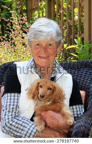 Smiling senior lady age 75,  in the garden with her dachshund dog.  - stock photo