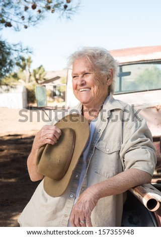 Smiling senior lady leaning against a vintage pickup truck holding a hat - stock photo