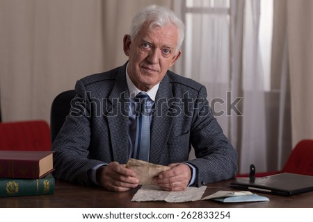 Smiling senior lawyer working in law firm - stock photo