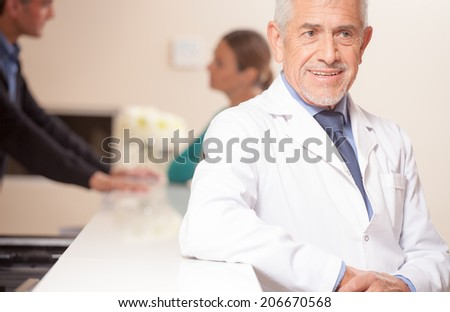 Smiling senior male doctor smiling at hospital reception desk, female patient speaking with young doctor on background.