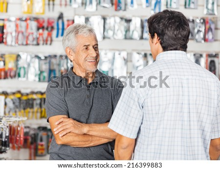 Smiling senior man conserving with son in hardware store