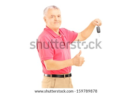 Smiling senior man holding a car key and giving thumb up isolated on white background - stock photo