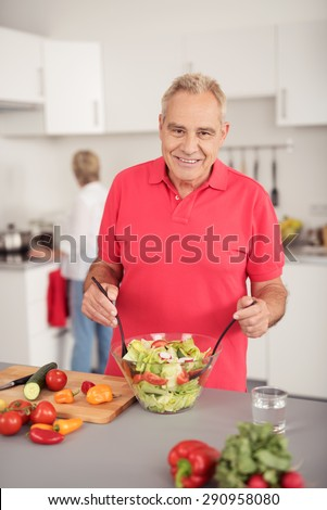 Smiling Senior Man in Casual Red Shirt, Looking at the Camera While Preparing Fresh Veggie Salad at the Kitchen - stock photo
