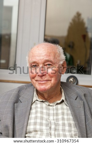 smiling senior man sits at the chair and looks happy - stock photo