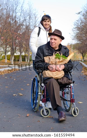 Smiling senior man sitting in a wheelchair with a bag of groceries on his lap being pushed along the street by a daughter or carer