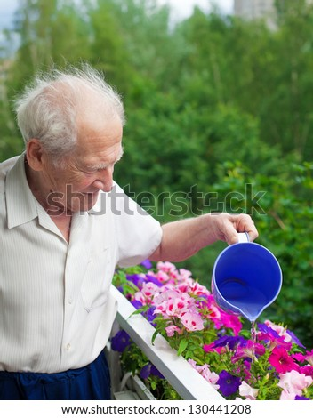 smiling senior man watering the flowers on his balcony - stock photo