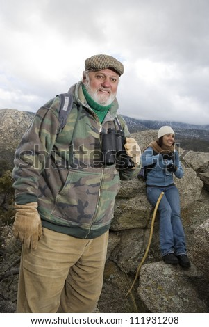 Smiling senior man with binoculars on a hiking