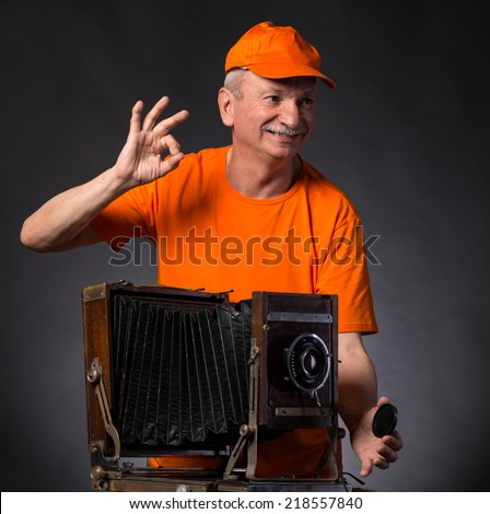 Smiling senior man with vintage wooden photo camera on a gray background - stock photo