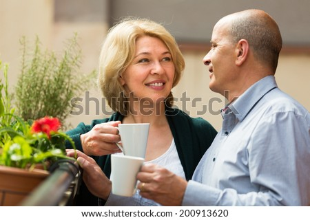 Smiling senior mature couple drinking tea and chatting on balcony  - stock photo