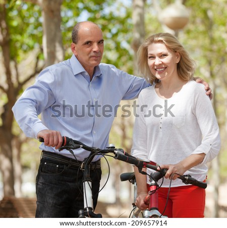 Smiling senior mature couple with bicycles enjoying a ride in public garden