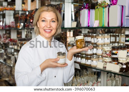 Smiling senior mature saleswoman offering delicious honey and marmalades in jars