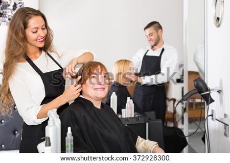 Smiling senior mature woman cutting hair in the barbershop - stock photo