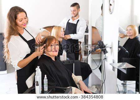 Smiling senior mature woman cutting hair in the hairdressing salon - stock photo