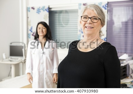 Smiling Senior Patient Standing With Doctor In Background