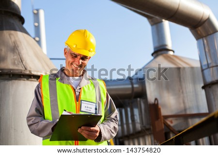smiling senior petrochemical engineer recording technical data on clipboard - stock photo