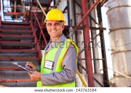 smiling senior petrochemical worker in plant - stock photo