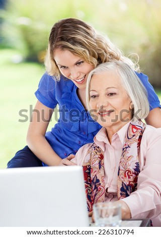 Smiling senior woman and granddaughter using laptop at nursing home porch - stock photo