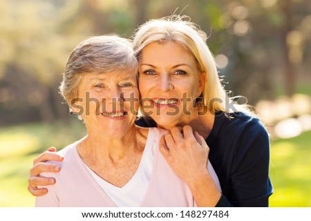 smiling senior woman and middle aged daughter outdoors closeup portrait - stock photo