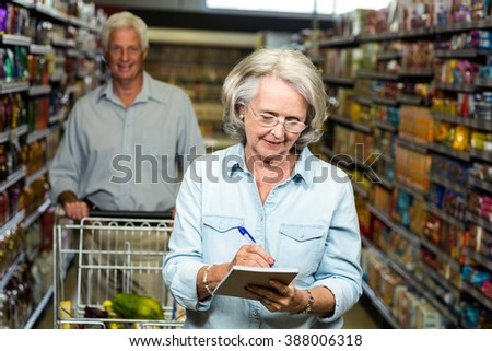 Smiling senior woman checking list at the supermarket
