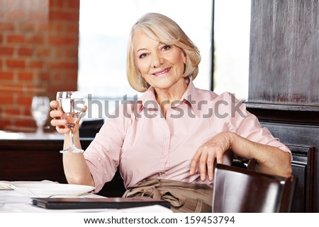 Smiling senior woman drinking a glass of water in a restaurant