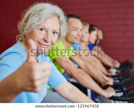 Smiling senior woman holding her thumbs up in spinning class in a fitness center - stock photo