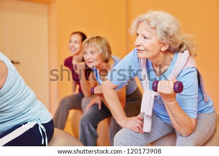 Smiling senior woman in a group doing back training exercises with dumbbells - stock photo