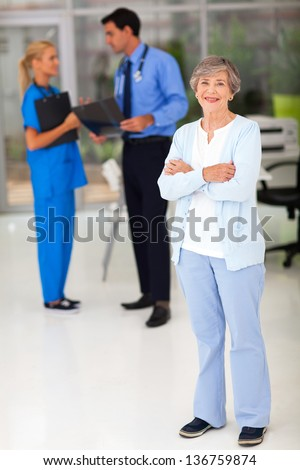smiling senior woman in hospital with her doctor and nurse on background - stock photo