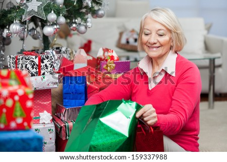 Smiling senior woman looking in bag while sitting by Christmas gifts at home - stock photo