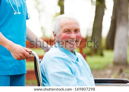 Smiling senior woman outdoors in wheelchair walked by nurse. - stock photo