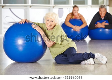 Smiling senior woman sitting with gym ball in a rehab center