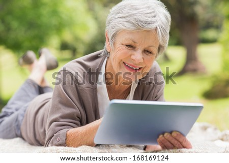Smiling senior woman using digital tablet while lying at the park - stock photo