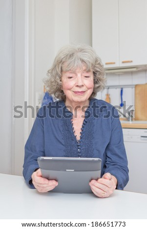 Smiling senior woman with e-book at her kitchen table, copy space