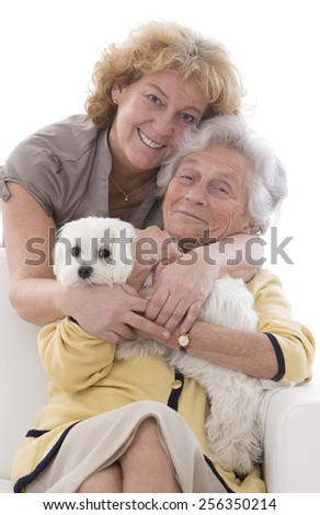 smiling senior woman with her dog  and middle aged daughter closeup portrait - stock photo