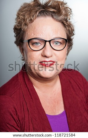 Smiling senior woman with short curly hair. Wearing glasses. Studio shot.