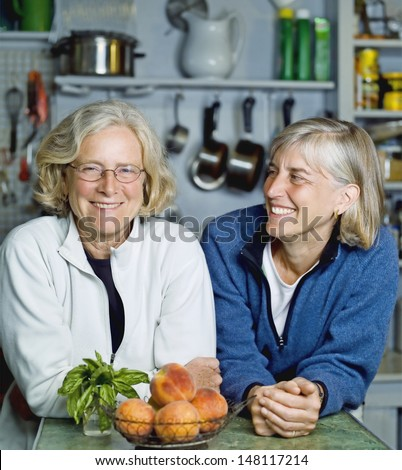 Smiling senior women leaning at kitchen counter - stock photo