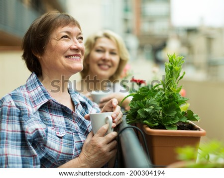 Smiling senior women staying on balcony with cup of coffee in hands  - stock photo