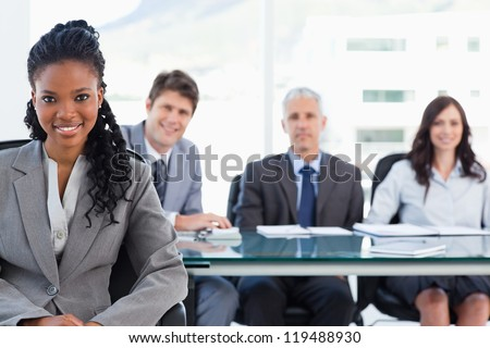 Smiling serious businesswoman sitting in front of her team - stock photo
