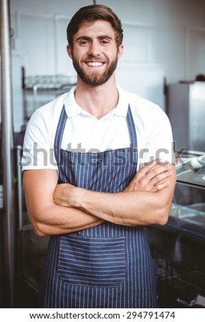 Smiling server in apron arm crossed at the bakery - stock photo