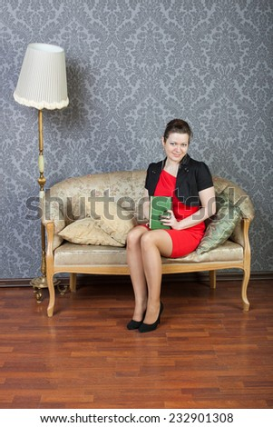 smiling sexy lass sits on a sofa and a read green book - stock photo