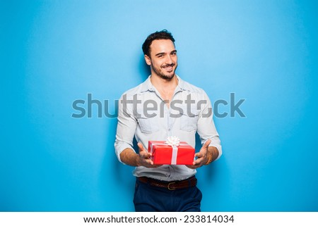 smiling sexy man on blue background with christmas gift - stock photo