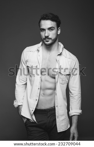 smiling sexy man with unbuttoned shirt and hands in pockets, black and white - stock photo