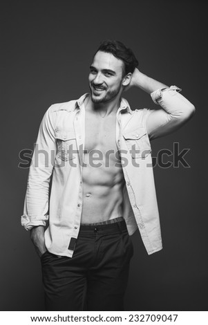 smiling sexy man with unbuttoned shirt and hands in pockets, black and white