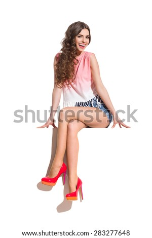 Smiling sexy woman  in pink top, jeans shorts and red high heels sitting on the top of white banner. Full length studio shot isolated on white. - stock photo
