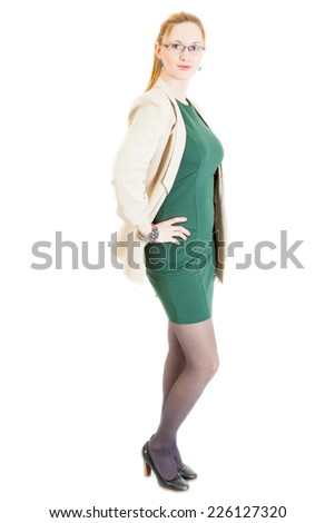 smiling sexy young blonde lass wearing a green dress, jacket, black panti-tights and sandals - stock photo