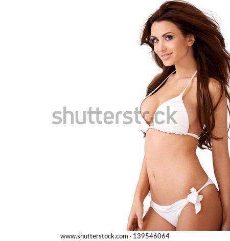 Smiling sexy young brunette woman with a lovely figure posing in a white bikini  three quarter isolated studio portrait - stock photo