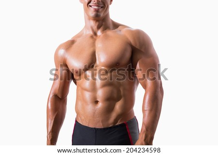 Smiling shirtless muscular man standing over white background - stock photo