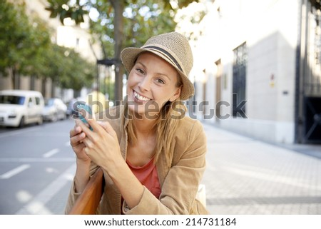 Smiling shopping girl using smartphone in town - stock photo