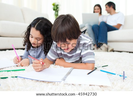 Smiling siblings drawing lying on the floor