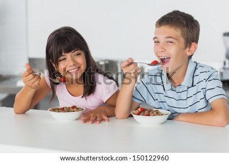 Smiling siblings eating cereal for breakfast in kitchen at home - stock photo